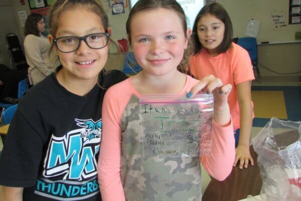 Students hold up a bag of bones from the owl pellet dissection.
