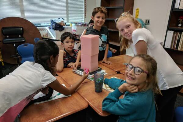 Students add a table stacking up foam blocks learning about earthquake resistant buildings