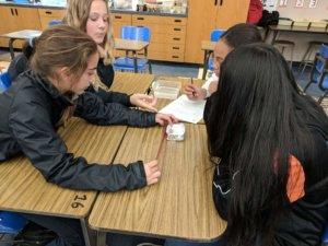 Students design aluminum foil boats.