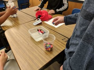 Students design a foil boat to see how much it can hold before sinking.