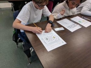 Students working at a table filling out worksheets.