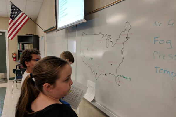 Students work at the whiteboard with a United States map.