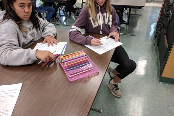 Students use colored pencils to fill in a worksheet.