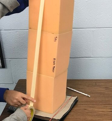 Students use tape to connect foam blocks on at shake table.