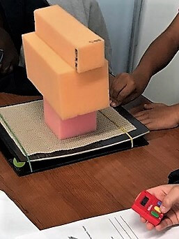 Students stack foam blocks on a shake table.