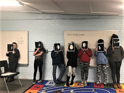 Students hold up photos of a face modeling the phases of the moon.