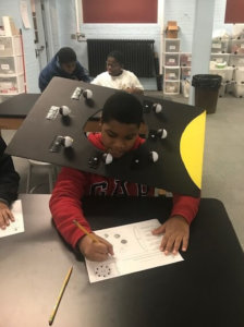 Students use boards with colored ping pong balls to model the phases of the moon.