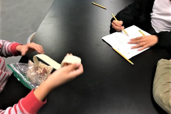 Students writing on a workseet and holding up masking tape.