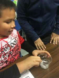 Students look at a cup of dry ice as it sublimates.