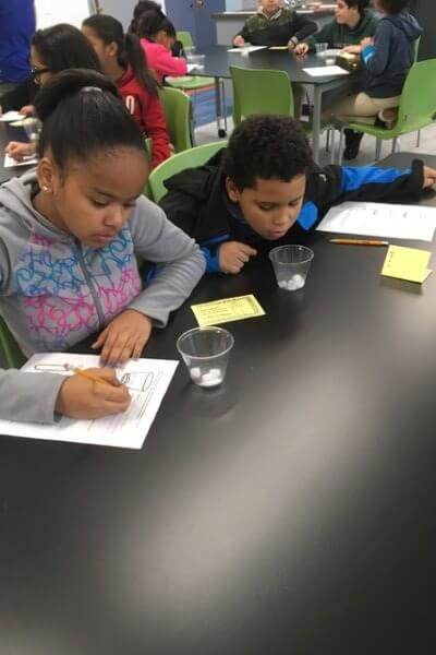 Students investigate dry ice in cups.