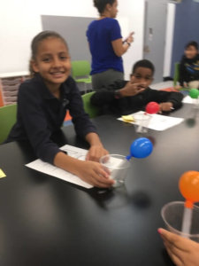 Students hold up test tubes with blown up balloons on top that have dry ice in the bottom.