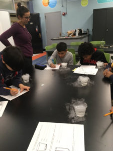 Students have dry ice in cups with water, creating water vapor around the cups.