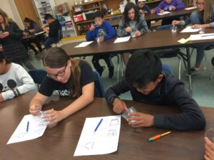 Students investigate dry ice in cups by pressing a metal spoon against the dry ice.