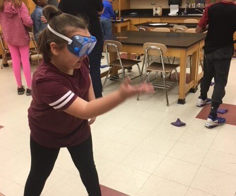 A student wearing goggles throws at a bean bag.
