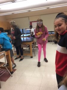 A student wearing goggles and holding bean bags while another student looks on.