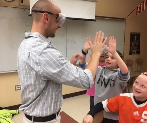 A teacher wearing googles high fives students.