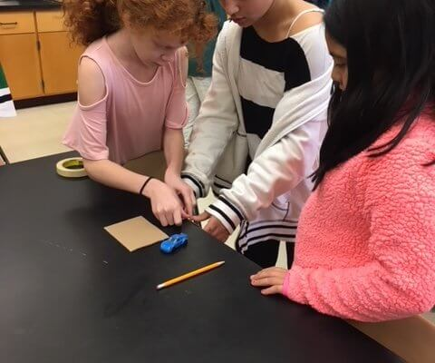 Students working at a table with tape cardboard, pencils and a matchbox car.