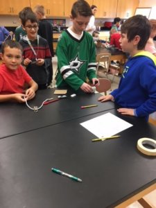 Students working at a table with pencils, tape, car, cardboard and rope to make a Rube Goldberg device.