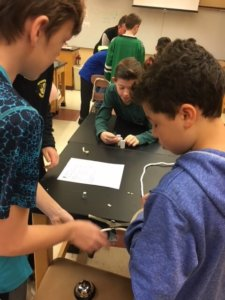 Students working at a table with rope, dominos, tape, and bell to make a Rube Goldberg device.