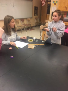 Two students working at a table with a funnel, ruler and tape.