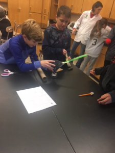 Students use materials to build a Rube Goldberg device to ring a bell.