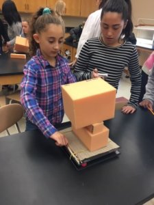 Students stack foam blocks on a shake table representing an earthquake.