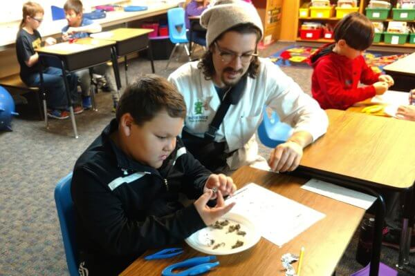 An instructor looks on as a student dissects an owl pellet.