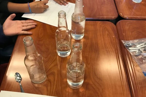 Glass bottles with varying amounts of water in them are shown.