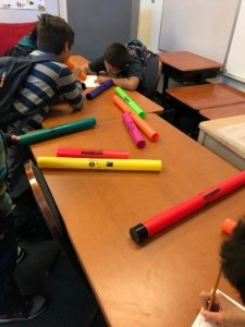 Students writing on worksheet with sound tubes on table.