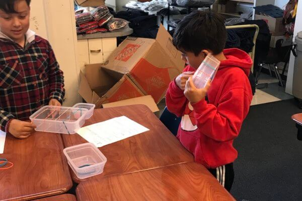 Student listens to sound elastic makes on plastic container.