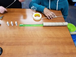 Studenst create a Rube Goldberg device with dominos, marbles, ruler, tube and funnel.