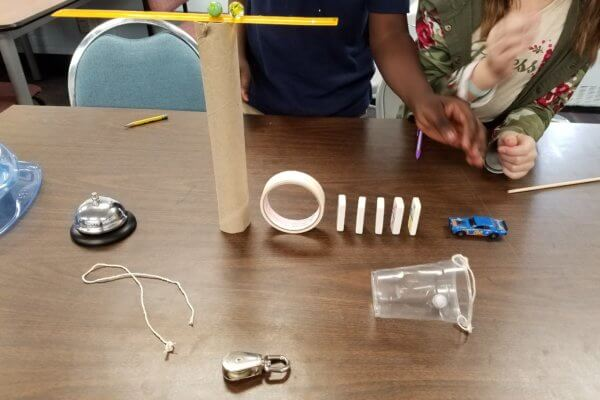 Students create a Rube Goldberg device with a bell, marbles, ruler, tape dominos and car.