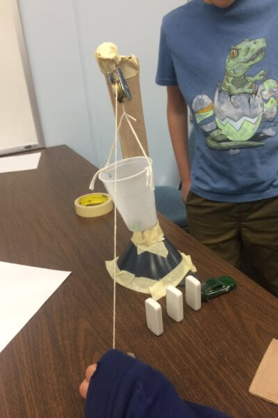 Students build a Rube Goldberg device.