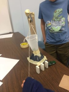 Students build a Rube Goldberg device.