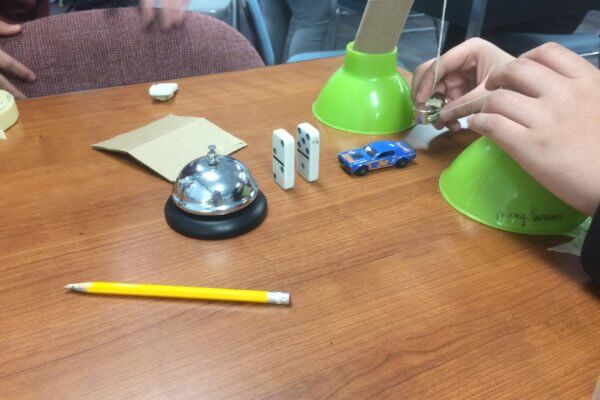 Students use a car, and dominos to ring a bell for their Rube Goldberg device.