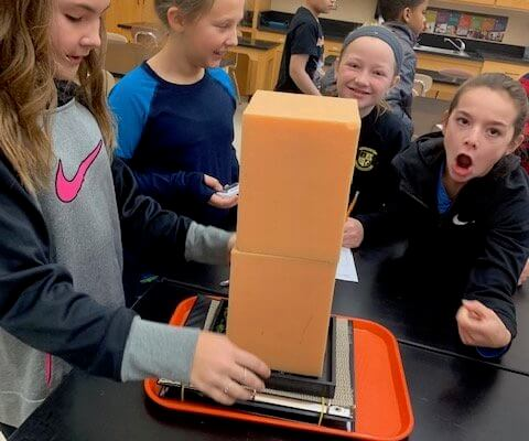 Student test a foam structure to see how an earthquake would effect it.