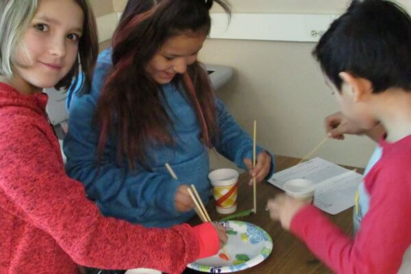 Students use chopsticks to fish wooden fish out of a plate.