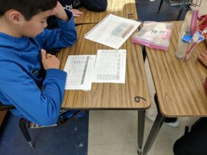 Student looks at a table on his worksheet.
