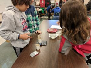 Students weigh cups with their mixture components.