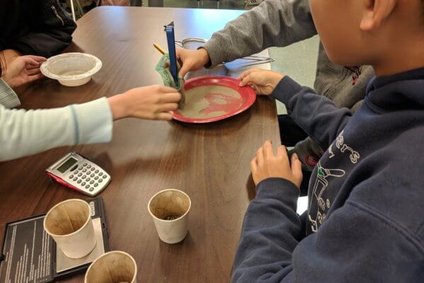 Students use a magnet over a mixture.