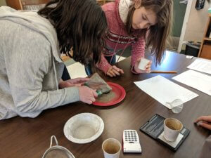 A student uses a magnet over a mixture while another student looks on.