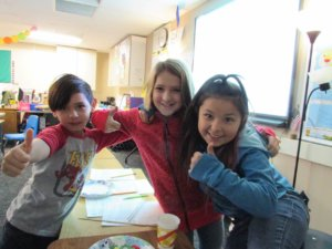 Three students give thumbs up.