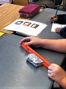 A student uses a ruler to measure a foil boat