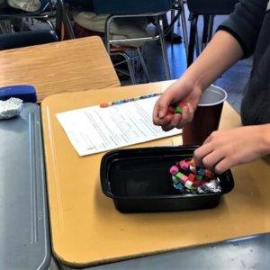 A student puts cubes into a foil boat.