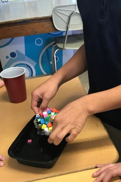 A student holds many small cubes on a boat over a container