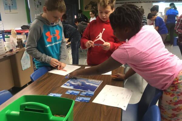 Students read cards during the water cycle game.
