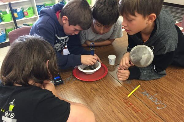 Students use a magnet in a mixture over a plastic bowl, sitting on a plate.