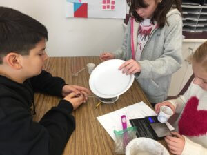 Student pours material into a strainer, while another student looks into a paper cup.