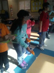Students wear goggles as they throw bean bags.