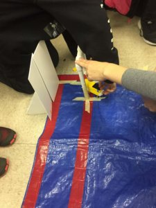 Students test their Lego design in the model hallway and classroom.